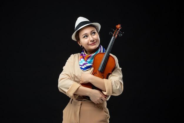 Vista frontal violinista feminina com chapéu segurando o violino na parede escura melodia instrumento performance música emoção mulher concerto