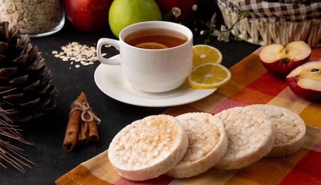 Vista frontal xícara de chá com fatias de limão e canela com maçãs em cima da mesa