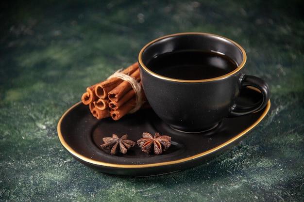Vista frontal xícara de chá em xícara preta e prato em superfície escura de vidro cerimônia de açúcar bolo de café da manhã sobremesa cor doce canela