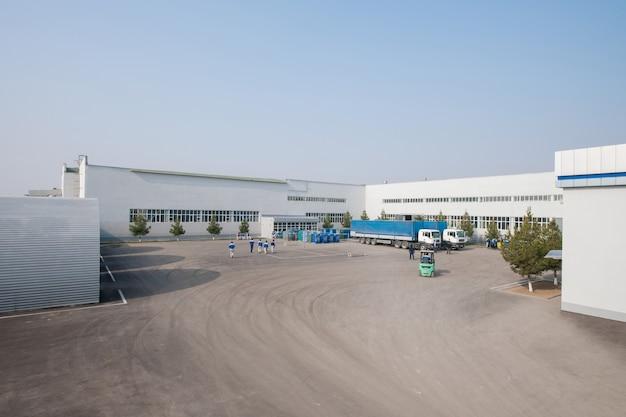 Vista geral da fábrica com caminhões e pessoas