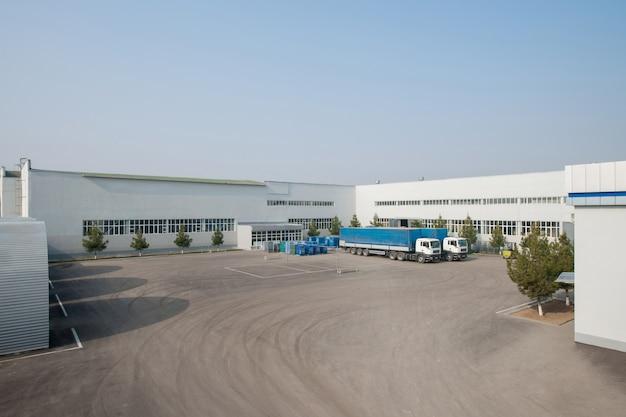 Vista geral da fábrica com caminhões. um caminhão no estacionamento da fábrica