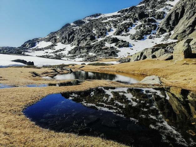 Vista hipnotizante da água refletindo os arredores na montanha penalara, na espanha