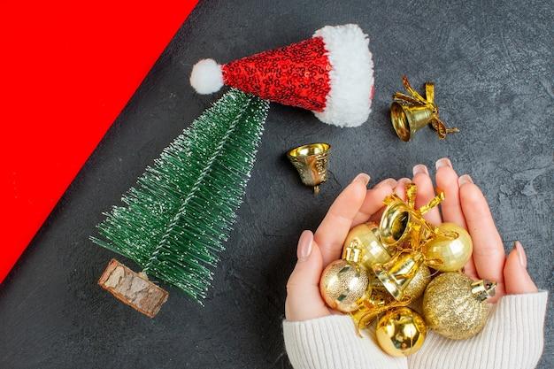 Vista horizontal da mão segurando a árvore de natal de acessórios de decoração chapéu de papai noel em um fundo escuro