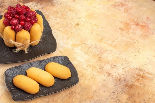 Vista horizontal da mesa posta com um bolo de presente e biscoitos para os convidados na mesa de cores misturadas