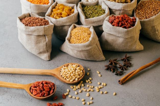 Vista horizontal de pequenos sacos com vários ingredientes secos coloridos, duas colheres de pau e anis estrelado próximo. conceito de dieta saudável