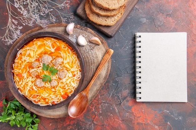 Vista horizontal de uma deliciosa sopa de macarrão com frango na tábua de madeira, verdes, colher, alho, tomate e, caderno, no fundo escuro