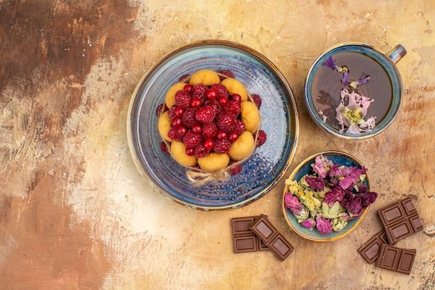 Vista horizontal de uma xícara de bolo macio de chá quente de ervas com barras de chocolate de frutas e flores