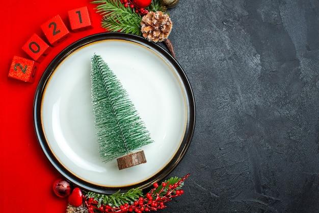 Vista horizontal do fundo do ano novo com a árvore de natal, acessórios de decoração da placa de jantar, ramos de abeto e números num guardanapo vermelho sobre uma mesa preta