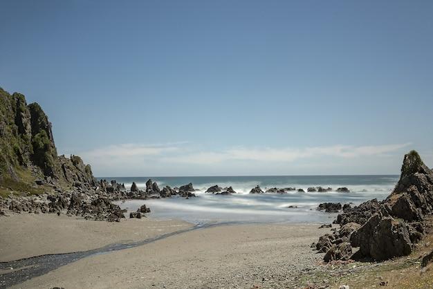 Vista idílica da costa arenosa entre penhascos
