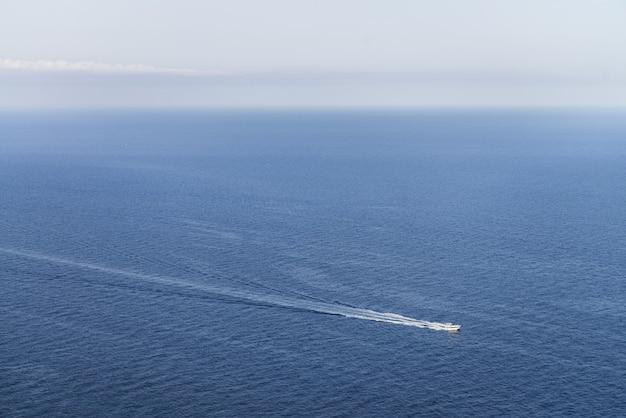 Vista idílica de um barco em um oceano azul com um horizonte claro - perfeito para papel de parede