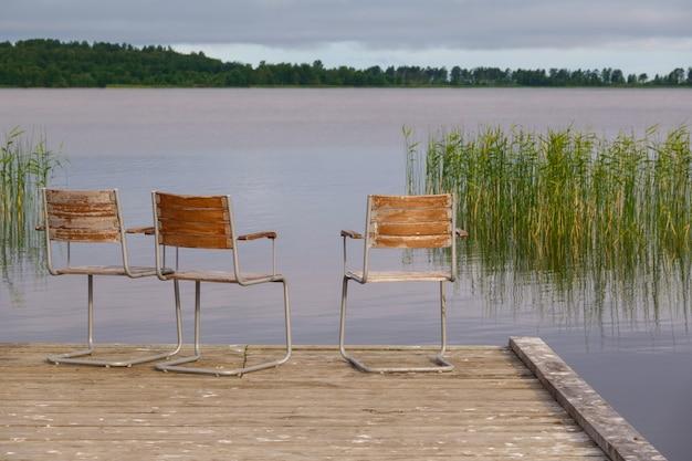 Vista idílica do píer de madeira no lago com cadeiras para negociações
