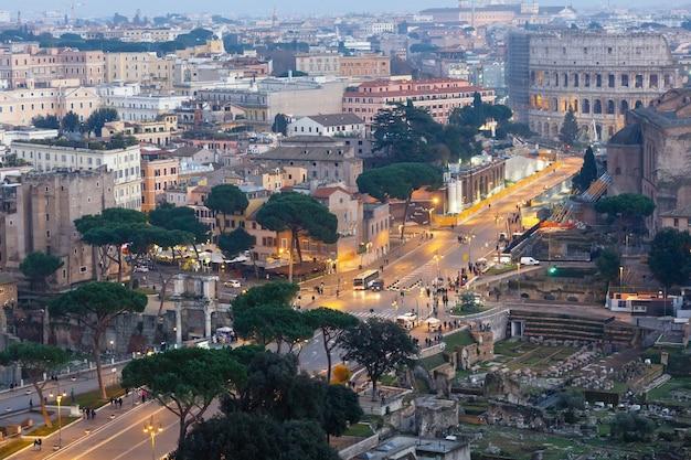 Vista iluminada da noite da cidade de roma do topo ii vittoriano. povos irreconhecíveis.