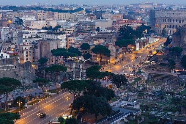 Vista iluminada da noite da cidade de roma do topo ii vittoriano.