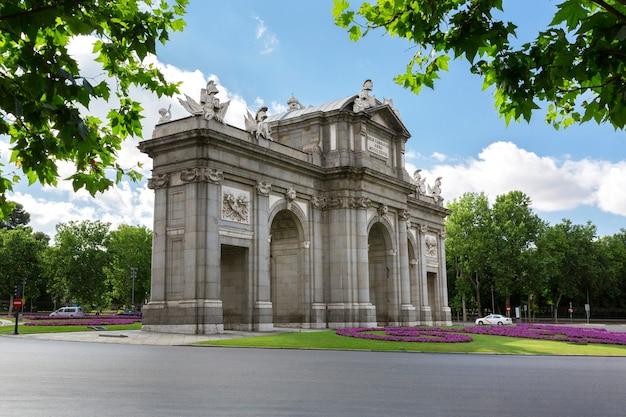 Vista incomum da puerta de alcala com o parque retiro atrás dela. locais famosos da cidade de madrid.