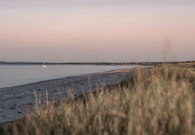 Vista incrível da colina da praia no fundo do belo pôr do sol