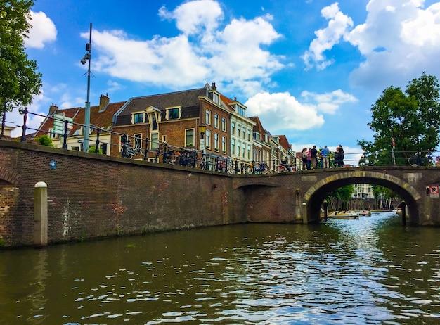Vista incrível de belos edifícios, bicicletas, uma ponte com um grupo de pessoas e barcos turísticos
