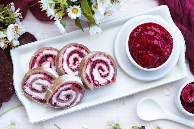 Vista incrível de deliciosos rolos de framboesa e geléia de framboesa colocados em um prato branco
