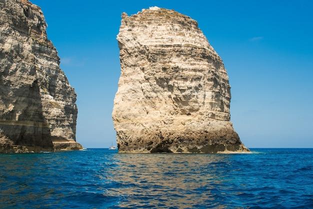 Vista incrível de imensas formações rochosas em águas calmas do mar