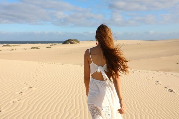 Vista incrível de uma jovem caminhando descalça nas dunas do deserto ao pôr do sol em corralejo, fuerteventura