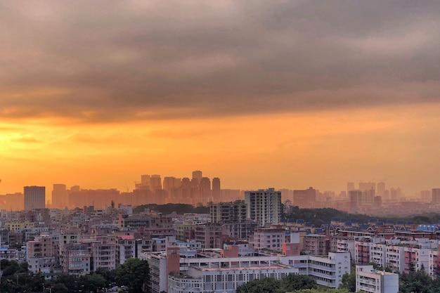 Vista incrível de uma paisagem urbana com o céu nublado com o pôr do sol laranja