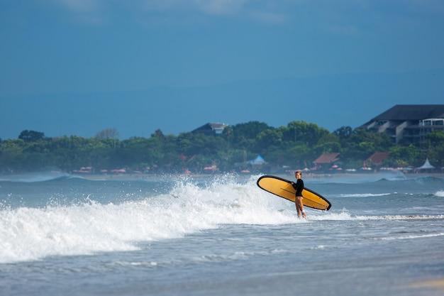Vista incrível. linda garota em pé com uma prancha de surf na costa do oceano