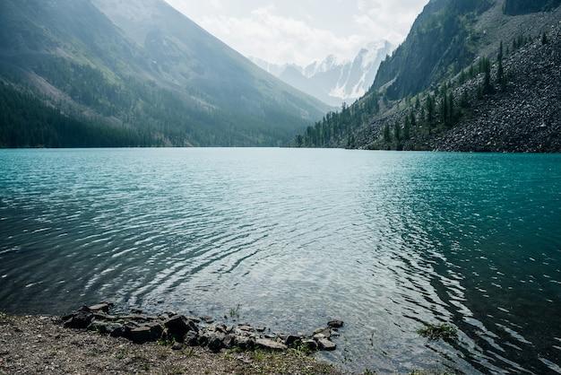 Vista incrível para ondulações meditativas na água calma clara azul do lago de montanha no fundo das montanhas nevadas.