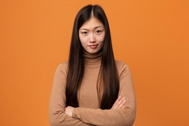 Vista infeliz da mulher consideravelmente chinesa dos jovens in camera com expressão sarcástica.