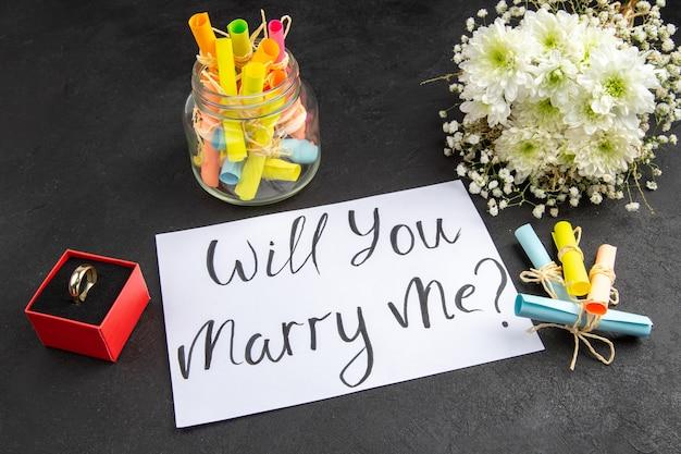 Vista inferior anel de noivado na caixa buquê de flores pergaminho desejos papéis na jarra quer se casar comigo escrito no papel na mesa