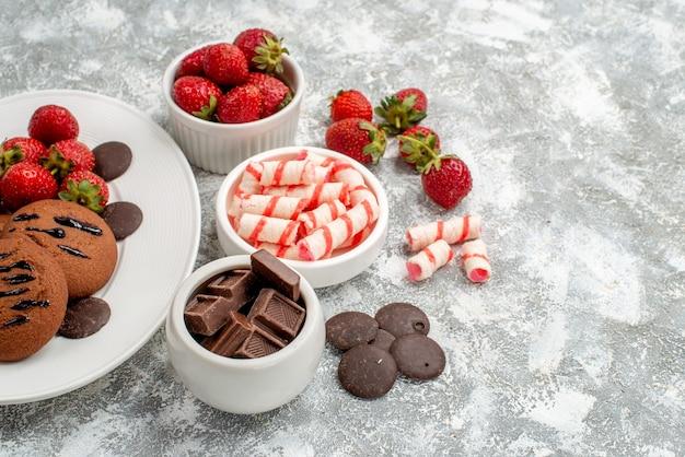 Vista inferior biscoitos morangos e chocolates redondos no prato oval branco taças de chocolates doces e morangos no lado esquerdo da mesa cinza-esbranquiçada
