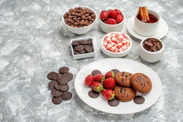 Vista inferior biscoitos morangos e chocolates redondos no prato oval tigelas com doces, morangos, chocolates, cereais e chá de canela na mesa cinza-esbranquiçada