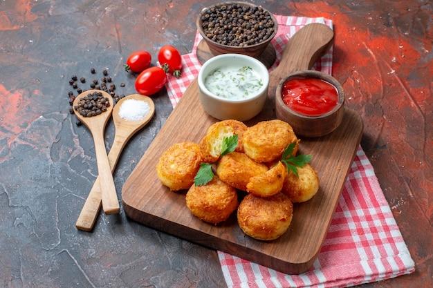 Vista inferior, bolas de queijo, molhos em tigelas na tábua de madeira, tomate cereja, colheres de pau, pimenta preta em fundo escuro