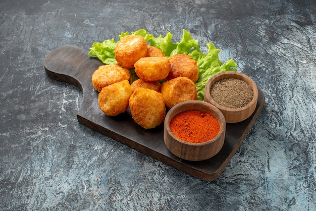 Vista inferior, bolinhas de queijo frito, alface, tigelas de especiarias na tábua de cortar na mesa
