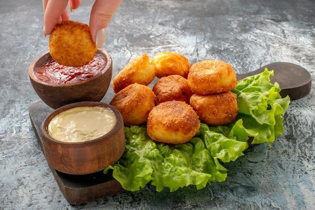 Vista inferior bolinhas de queijo frito tigelas de molho de alface na tábua de cortar bolinho de queijo na mão feminina