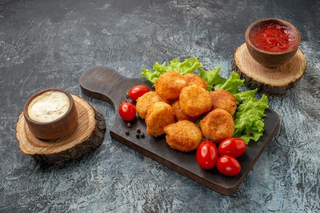 Vista inferior bolinhas de queijo frito, tomate cereja, alface em tigelas de molho em tábuas de madeira