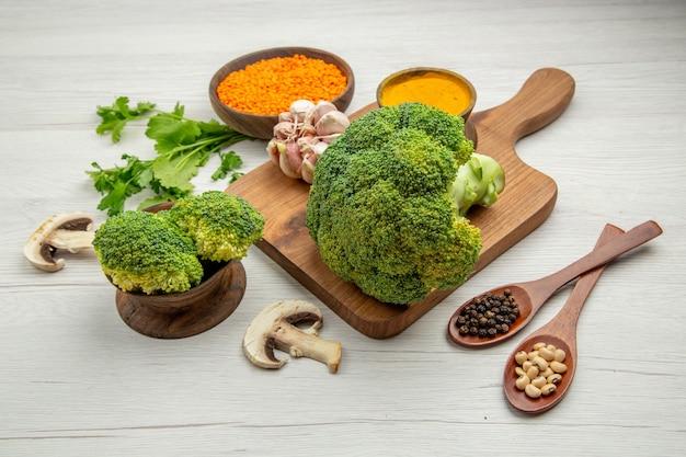 Vista inferior, brócolis fresco, alho, açafrão, na tábua, cogumelos, tigela, lentilha, salsa, colheres de madeira, mesa cinza