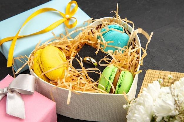Vista inferior caixa em forma de coração com macarons anel de noivado buquê de flores em fundo escuro
