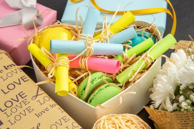 Vista inferior caixa em forma de coração com notas adesivas enroladas e macarons embrulhados em presentes em fundo escuro