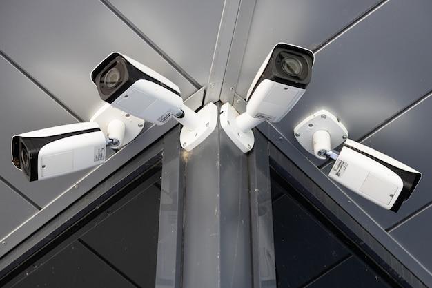 Vista inferior close-up de quatro câmeras de vigilância brancas