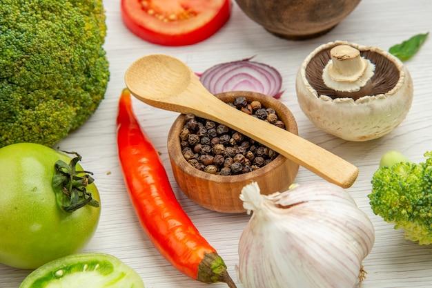 Vista inferior, colher de pau de alho e brócolis pimenta preta na tigela de especiarias, cogumelo na mesa cinza