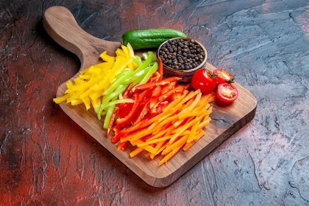 Vista inferior colorida pimenta cortada pimenta preta tomate pepino em uma tábua na mesa vermelha escura