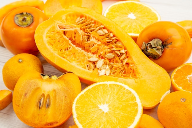 Vista inferior com fatias de abóbora, metade tangerinas e caquis laranja