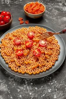 Vista inferior. corações de massa italiana cortam tomate cereja em prato oval garfo macarrão com coração vermelho em uma tigela na mesa cinza