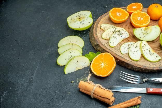 Vista inferior cortando maçãs e tangerinas com pó de hortelã seco na tábua de madeira, canela, garfo e faca no espaço livre da mesa escura
