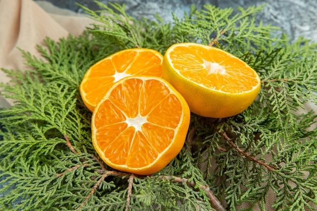 Vista inferior, corte de laranjas em galhos de pinheiro em superfície escura