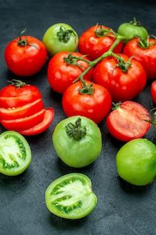 Vista inferior corte de tomates tomate verde vermelho na mesa escura
