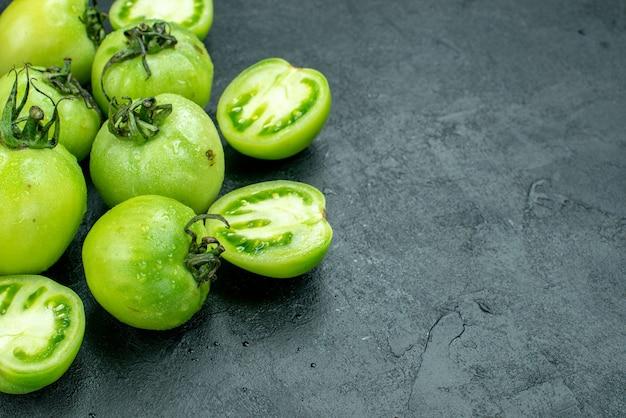 Vista inferior, corte de tomates tomates verdes no espaço livre da mesa escura