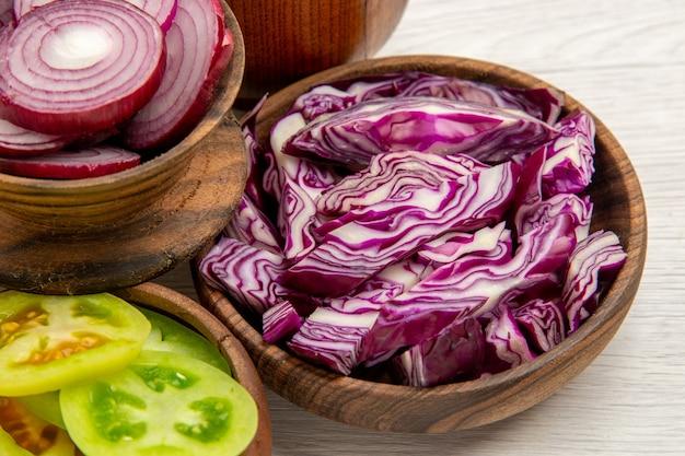 Vista inferior, corte de vegetais, corte de repolho roxo, corte de cebola, corte de tomates verdes em tigelas na mesa branca