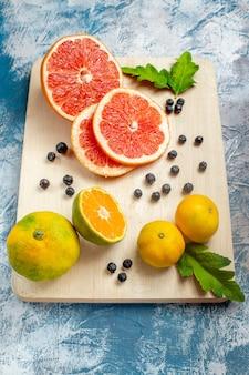 Vista inferior, corte laranjas e toranjas na tábua de cortar na superfície azul e branca