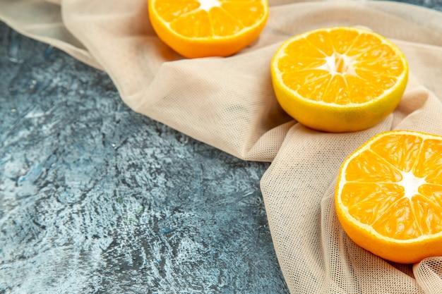 Vista inferior, corte laranjas em xale bege em superfície escura, espaço livre