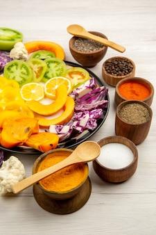 Vista inferior, corte legumes e frutas, abóbora, pimentão, caqui, repolho roxo, tempero, prato, preto, pequeno, tigela, colher de madeira, mesa de madeira